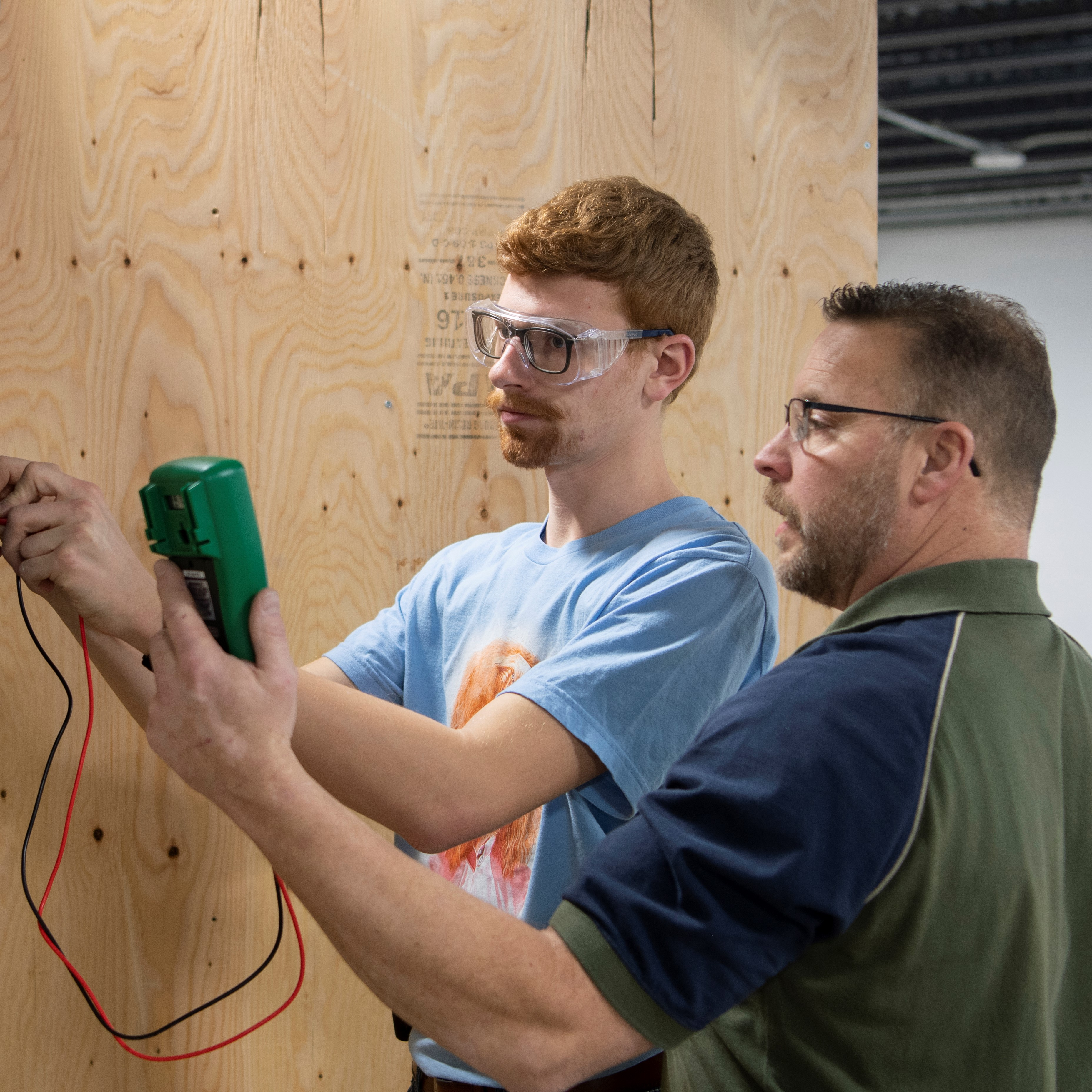 A student and his professor work on a plywood wall.