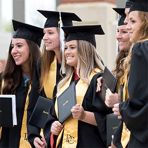 Female graduates hold their diplomas and smile.