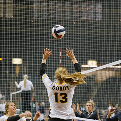 A volleyball setter hits the ball.