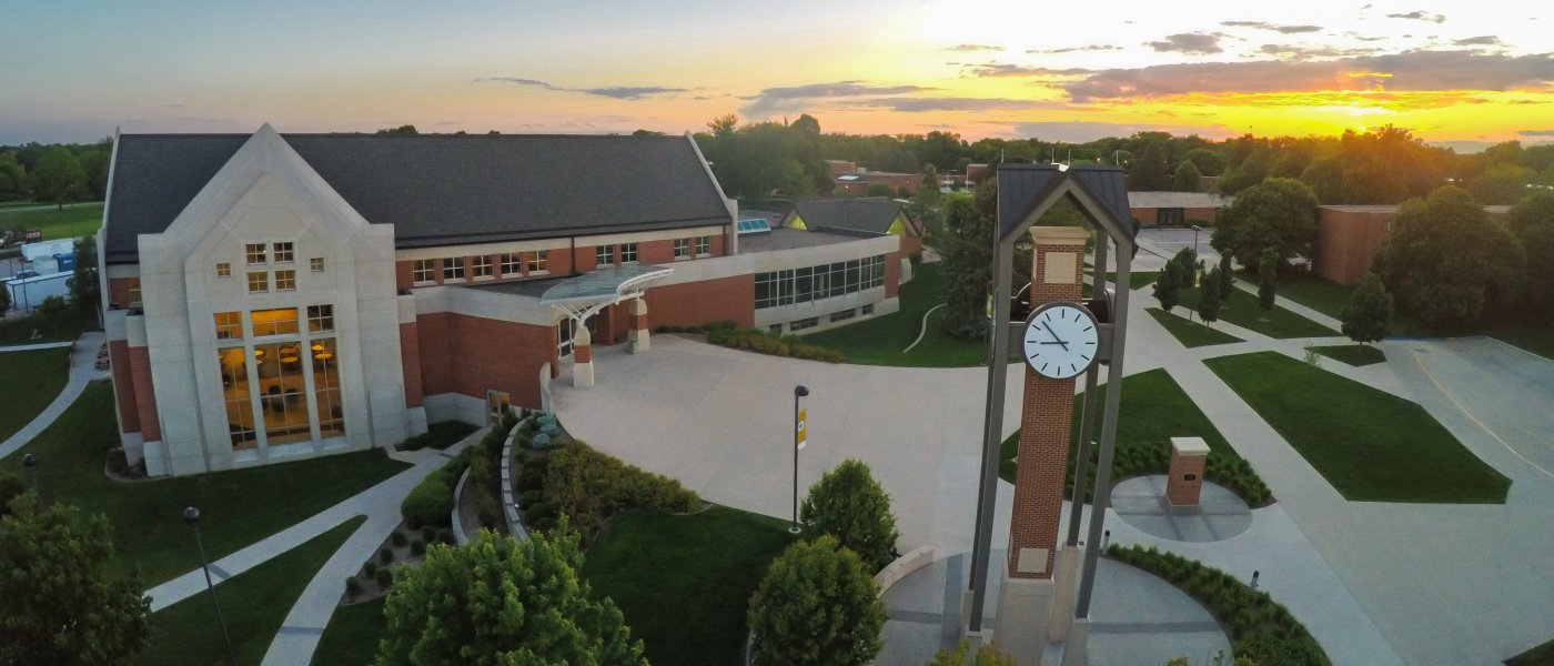 An arial shot of Dordt's campus at sunset, with a clock tower standing in front of a large brick building.