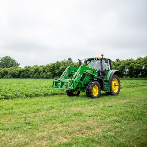 A tractor driving next to a soybean field.