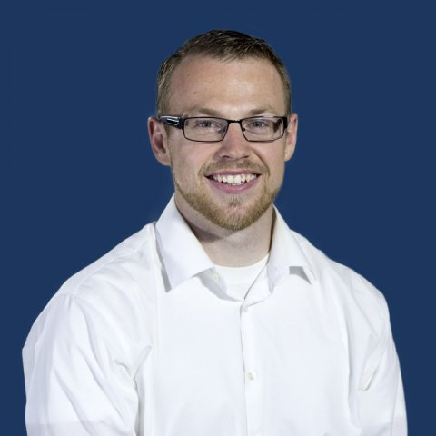A man in a white shirt smiling in front of a blue background.