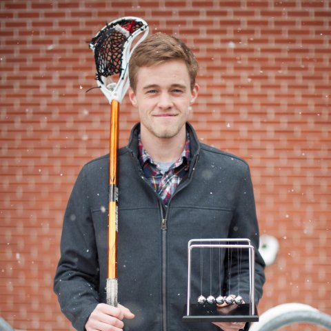 A male student holding a lacrosse pole.