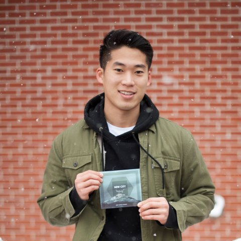 A smiling male student holding a CD.