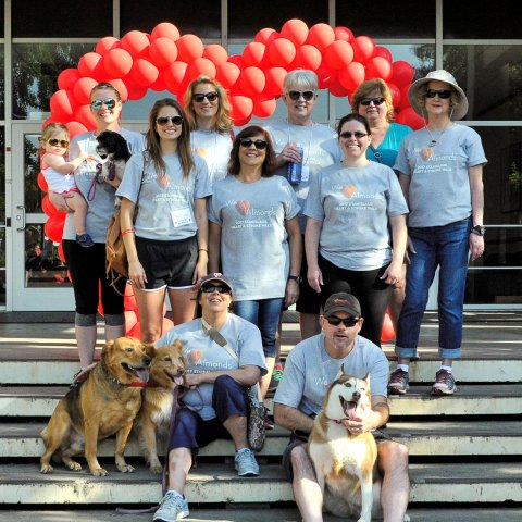 A group of people stand in front of a balloon arch shaped like a heart.
