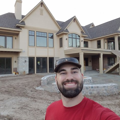 A smiling man in front of a house that is under construction.