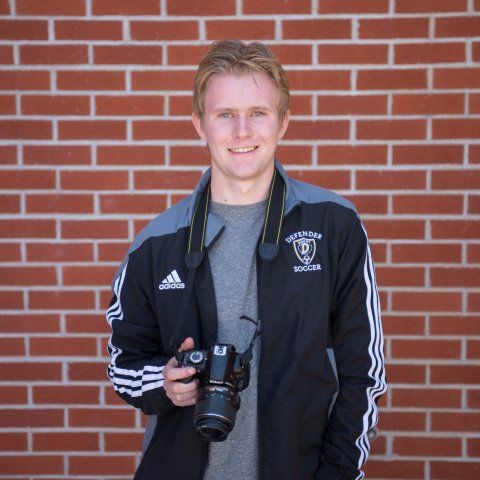 A smiling male student holding a camera.