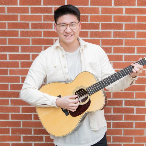 A smiling male student holding a guitar in front of a brick wall.