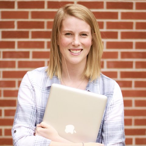 A female student holding a laptop.
