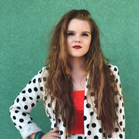 A female student in a polka-dotted blazer.