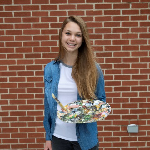 A female student holds an art palette in front of a brick wall.