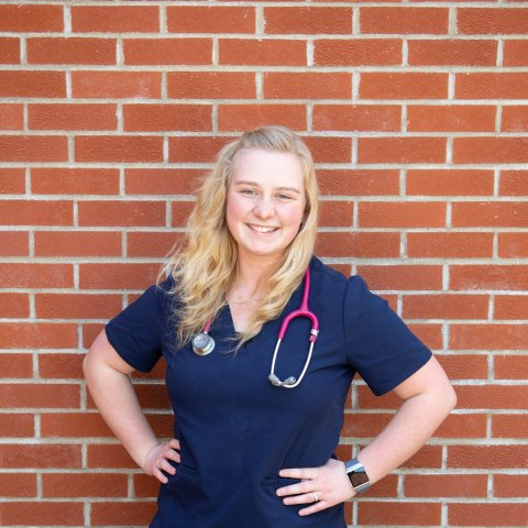A female student in a nursing uniform smiling in front of a brick wall.