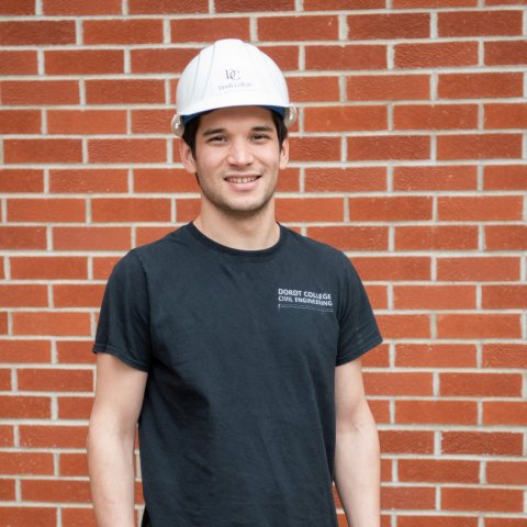 A male student wearing a construction hat in front of the brick wall.
