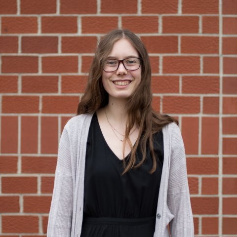A smiling female student stands in front of a brick wall.