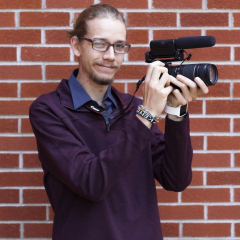 A male student holding a video camera.