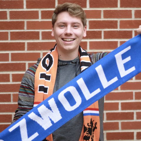 A male student holding a blue scarf.