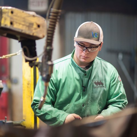 A male student works with machinery.