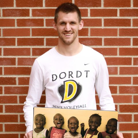 A male student holds a photograph of young kids.