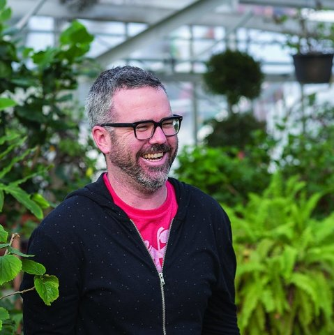 A man stands in a greenhouse.