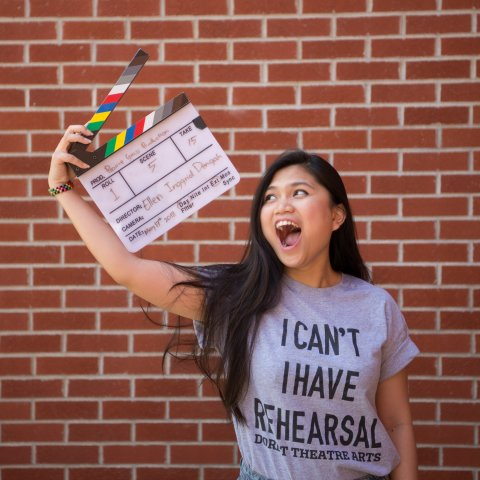 A female student holds a movie clapper.