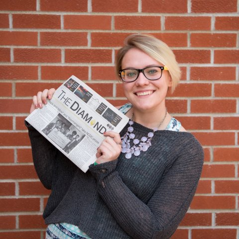 A smiling female student holding a newspaper.