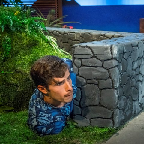 A male actor lying on the floor poking his head around a stone wall.