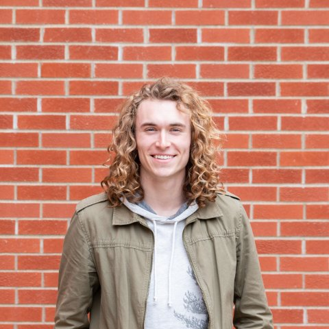 A male student stands in front of a brick wall.