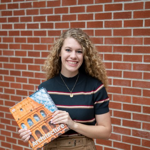 A female student holding a book of architecture in front of a brick wall.