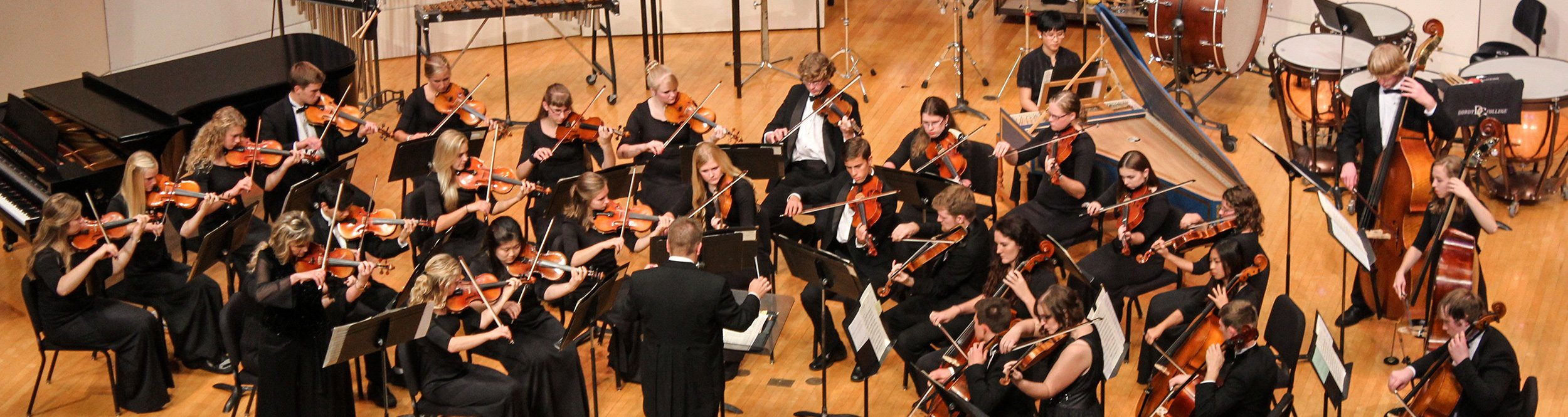 A string orchestra plays on stage.