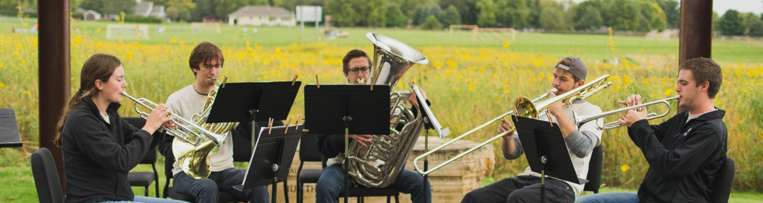 Four brass instrument players sit in a prairie playing their instruments.