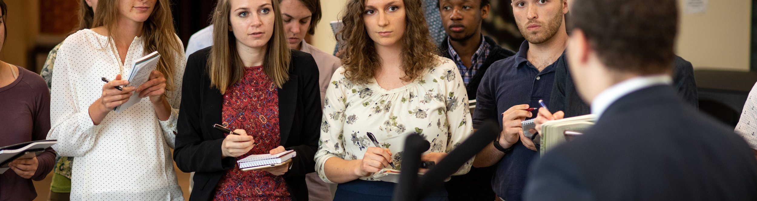 A group of journalism students ask questions at a man at a podium.