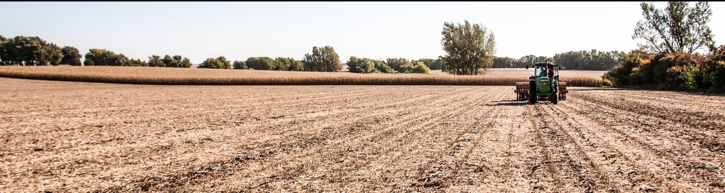 A tractor drives through an empty field.