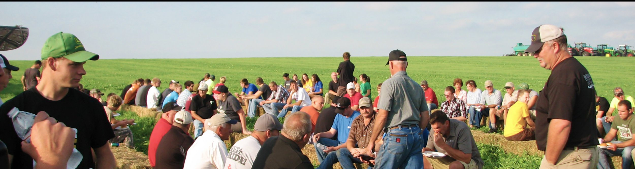 A group of people gathers in the fields.