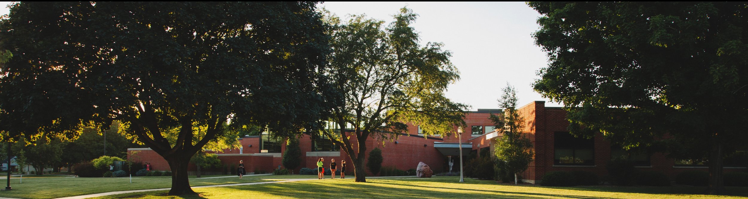 A large brick building with trees around it.