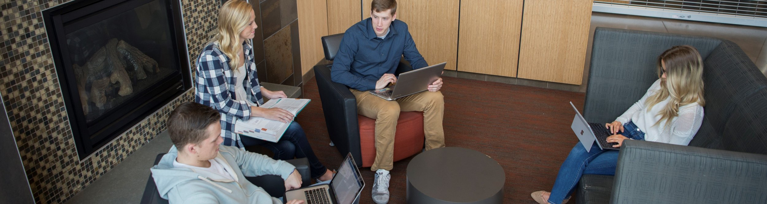 A group of students sit in a lounge area with their laptops.