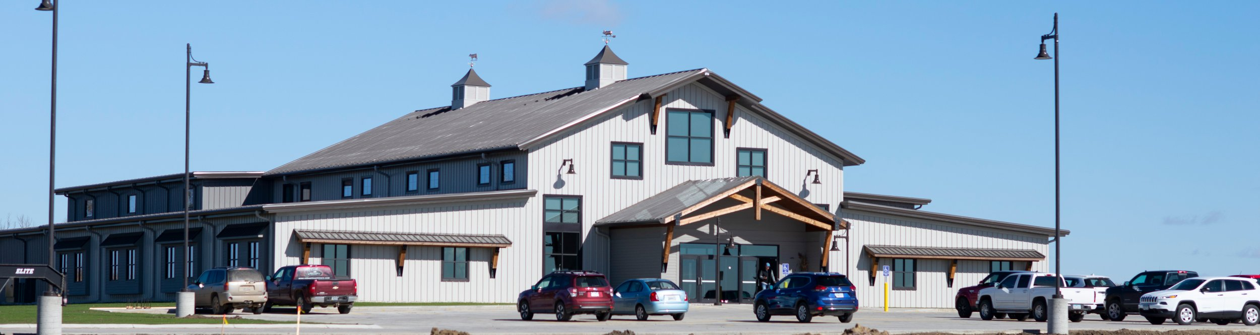 A large barn-like building with cars in front of it.