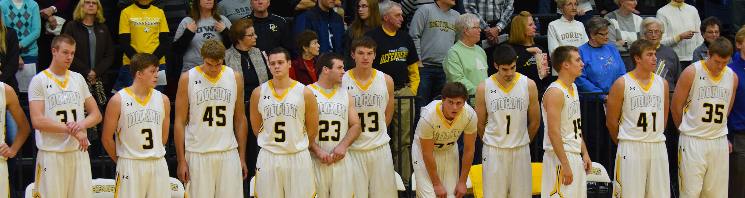 Male basketball players stand in a line by their bench.