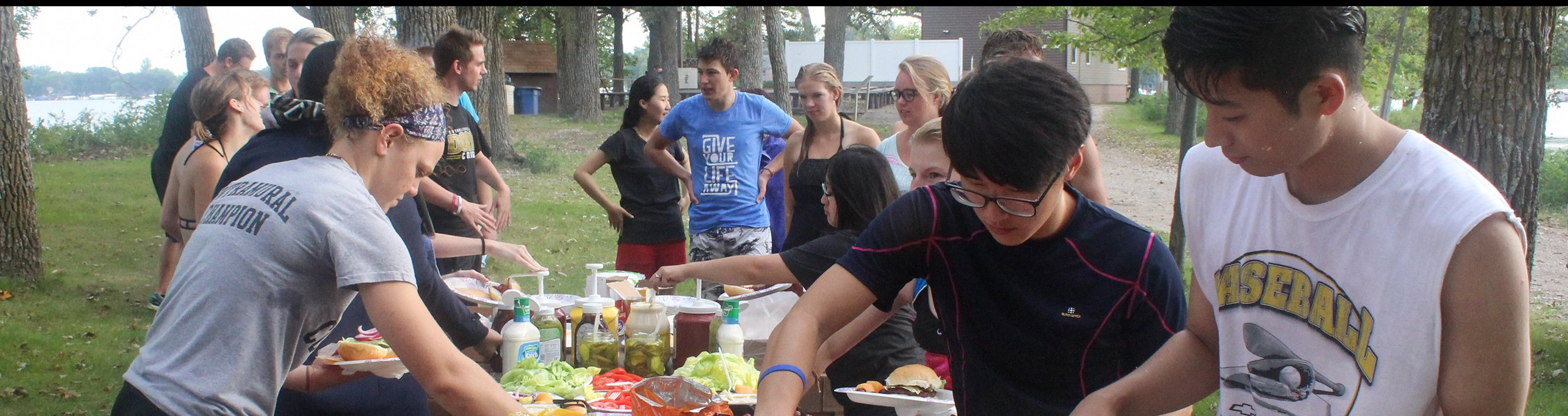 Students get food from a buffet line outdoors.