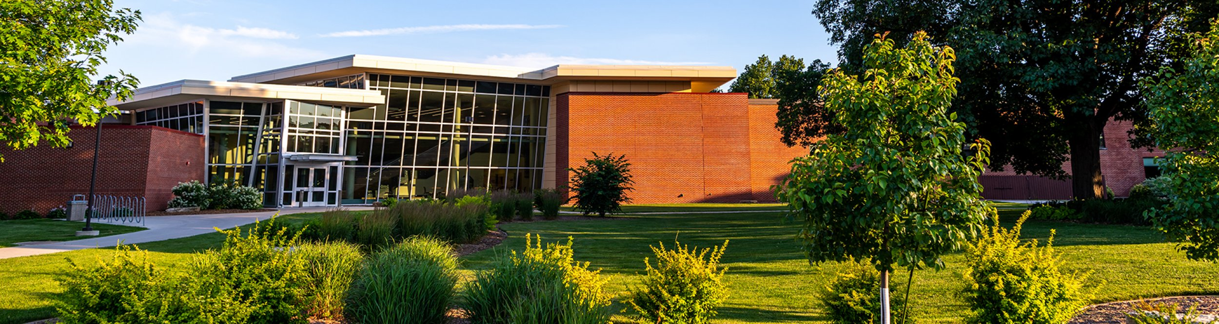 A large brick science building with a wall of glass windows.