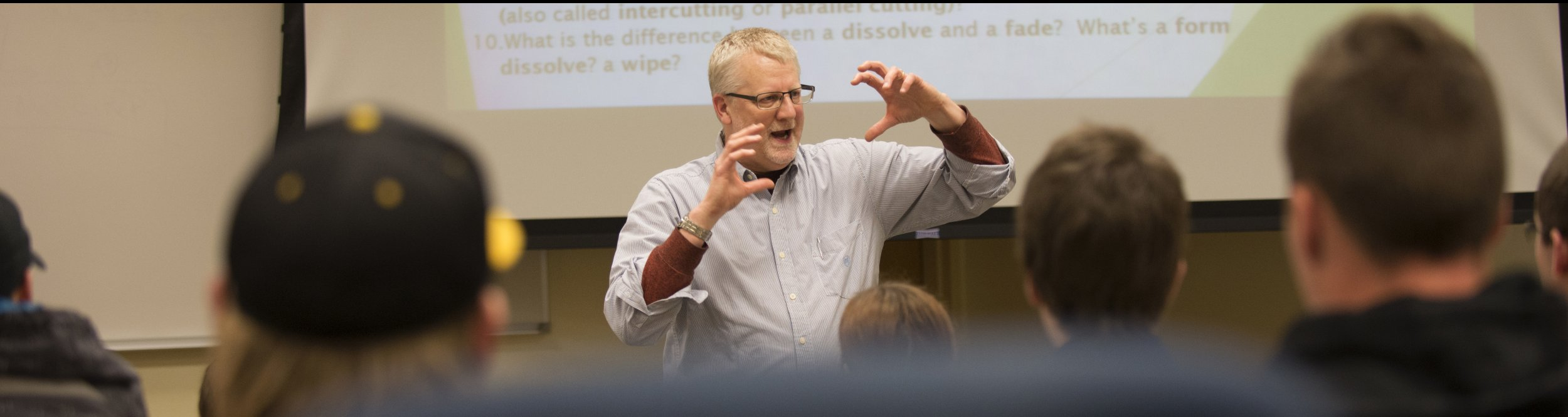 A professor gestures with his hands as he talks.