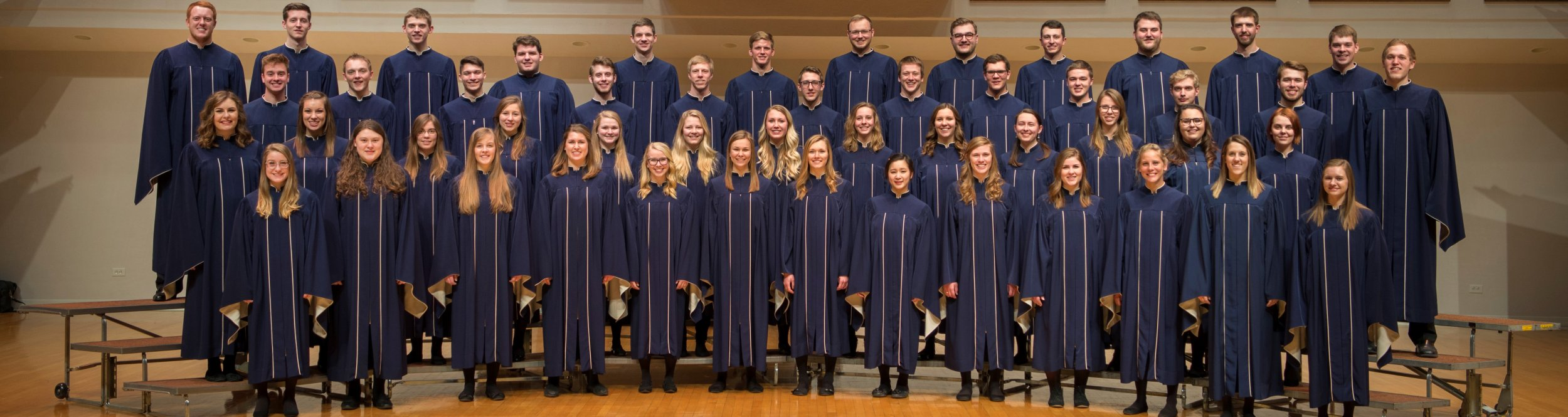 Students in choir robes stand on risers.