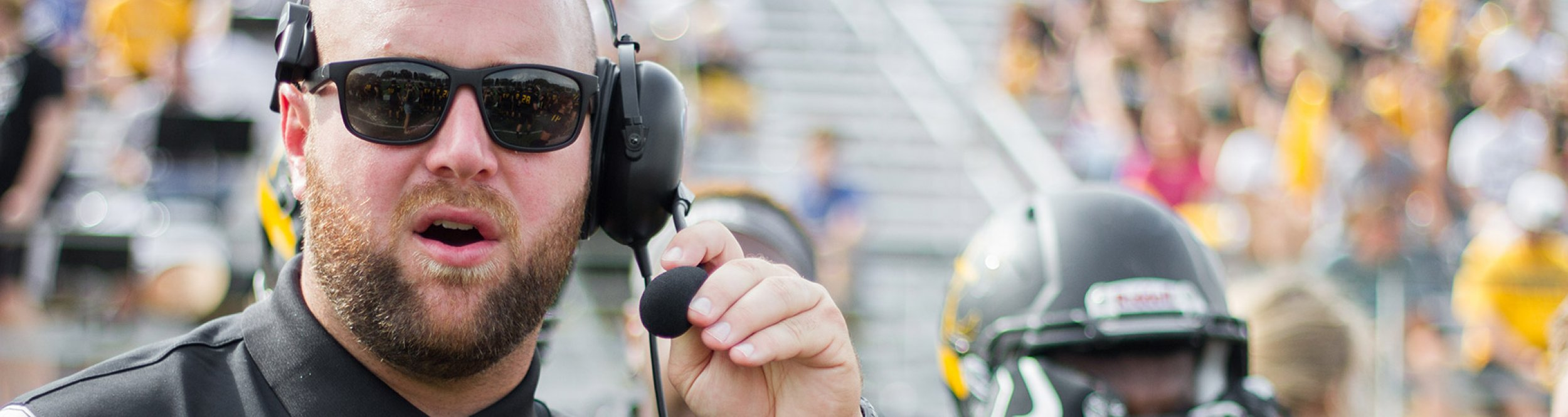 A football coach speaks into his headset.