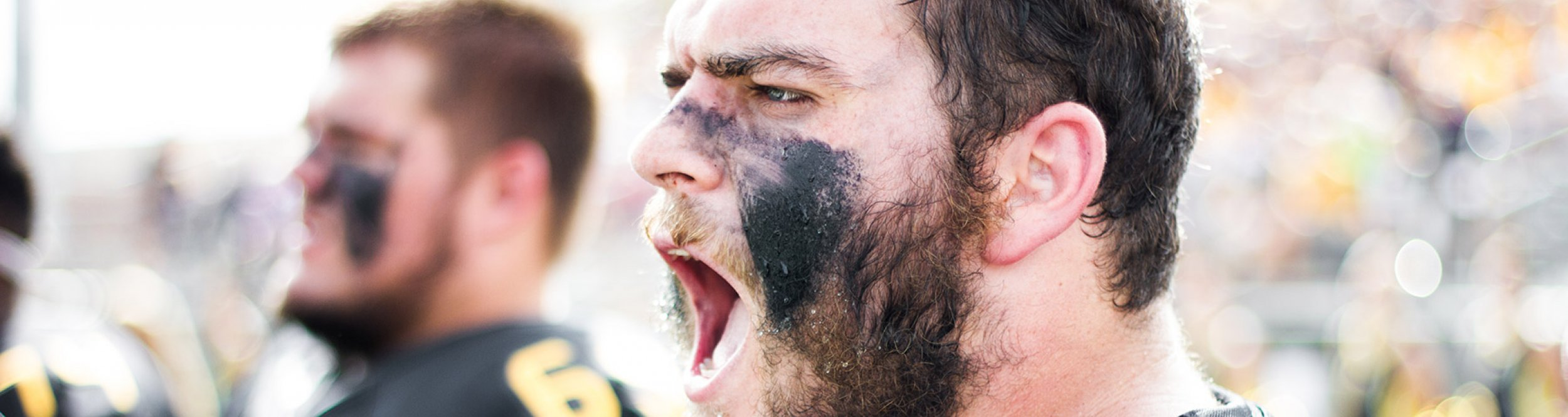 A football player with black paint on his face yells.