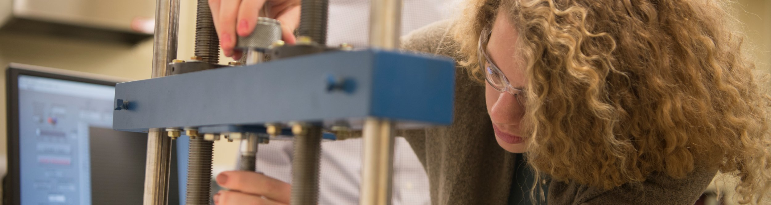 A female student inspects an engineering device.