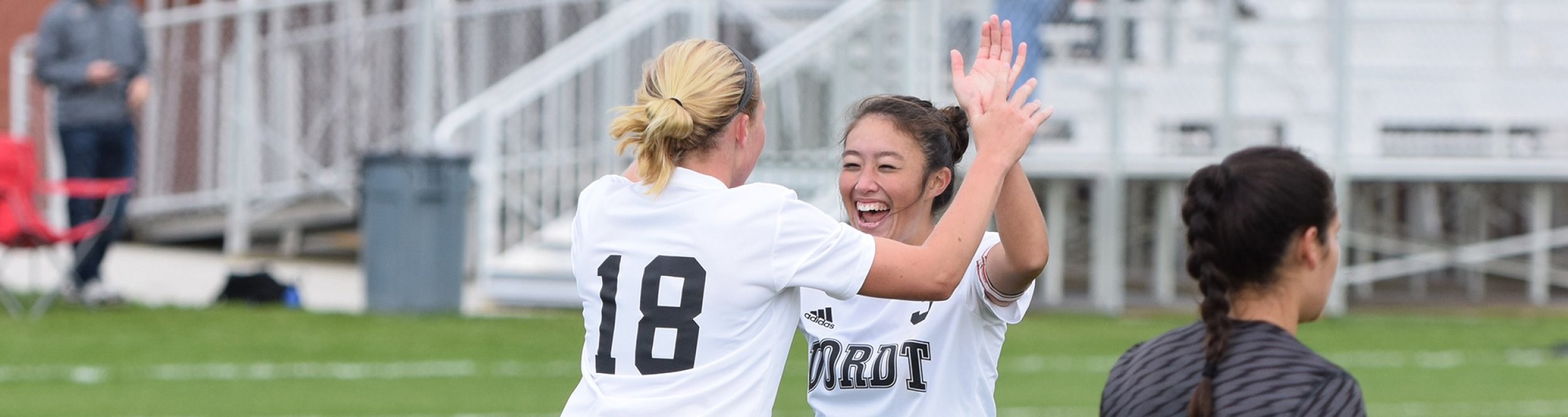 Female soccer players high five each other.
