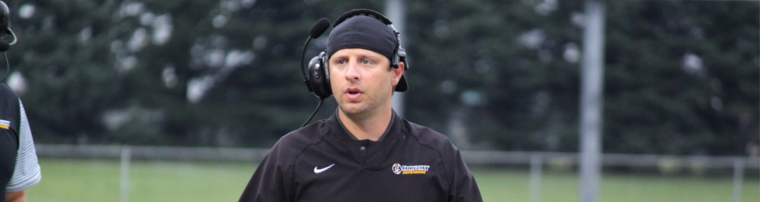 A football coach with a headset on.