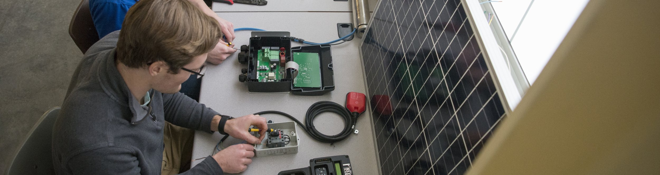 An engineering student works with a small device.
