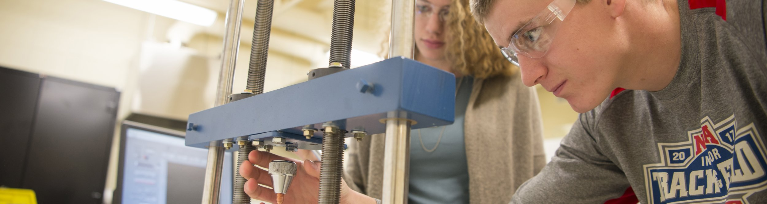 Two engineering students work on a metal device.
