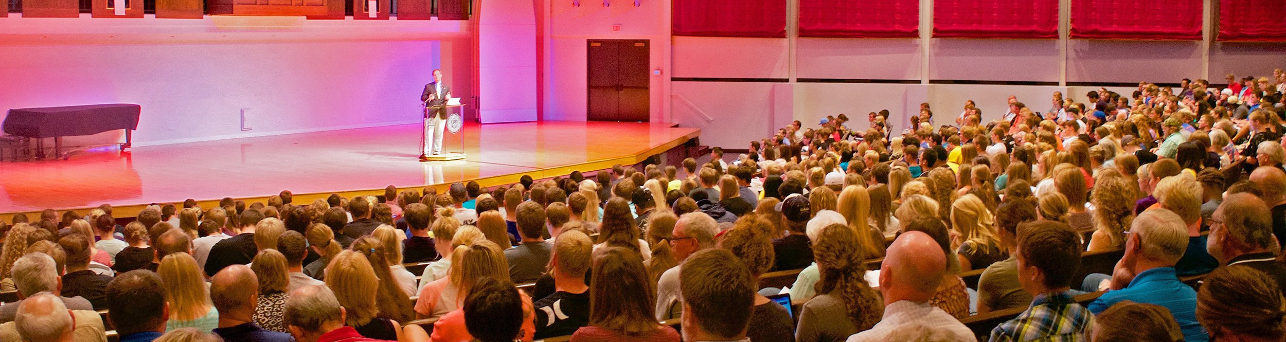 A speaker addresses a large crowd in an auditorium.