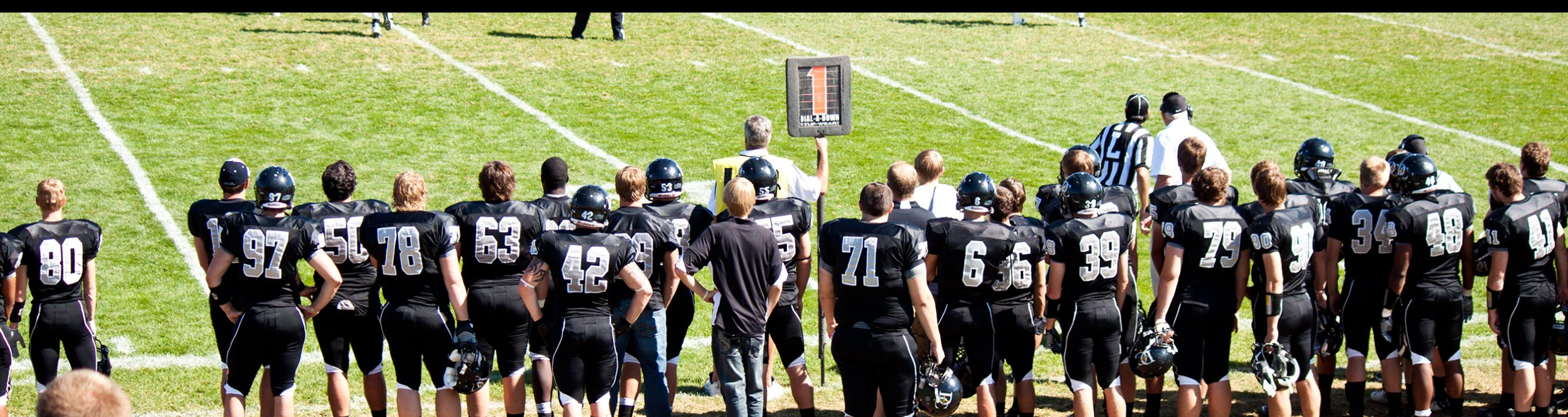 Dordt football players gather on the edge of the field.
